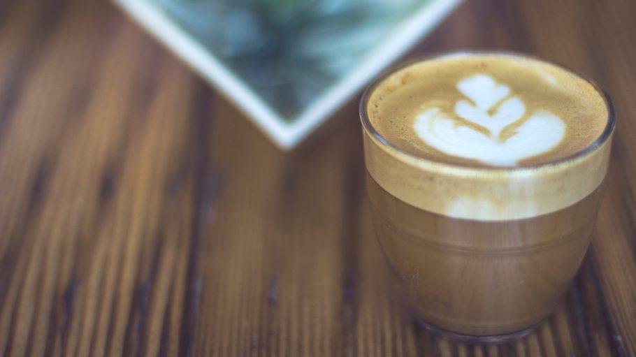 Kaffee mit Milchschaum auf Holztisch