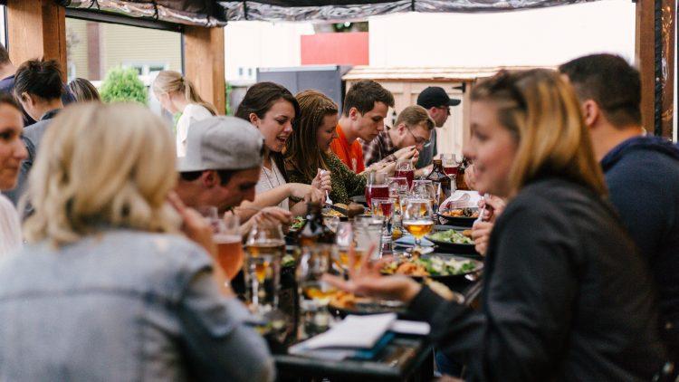 Gruppe von Menschen sitzt an einem langen Tisch mit Essen und Getränken.