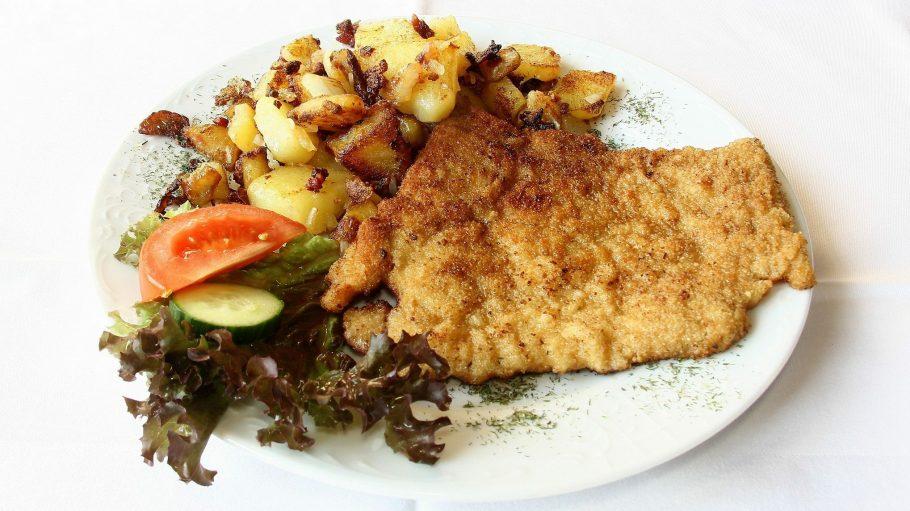 Paniertes Schnitzel auf einem Teller mit Bratkartoffeln und Salatgarnitur