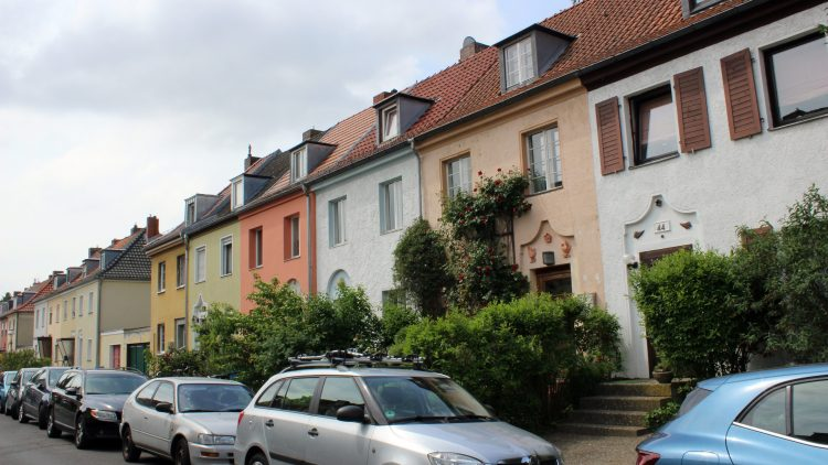 Kleine bunte Reihenhäuser in gelb, grün, orange, weiß und braun mit kleinen grünen Vorgärten im Fliegerviertel Tempelhof