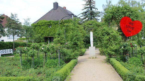 Grünanlage mit Mittelweg und einer weißen Skulptur, im Hintergrund mit Ranken bewachsenes Haus