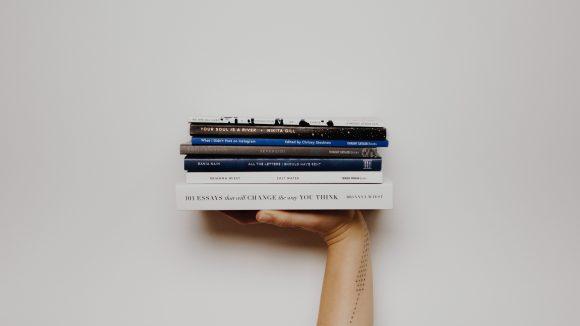 Eine Hand hält einen Stapel Bücher.