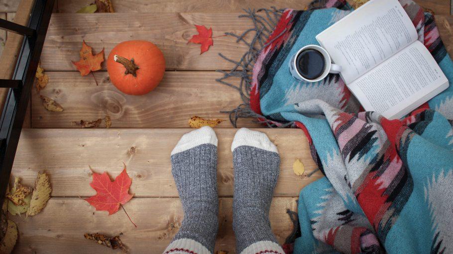 Warme Socken auf Holzdielen mit bunten Blättern, Kürbis und Decke.