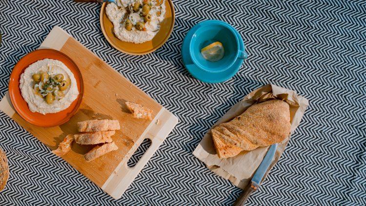 Hummus und helles Brot auf einer Picknick-Decke