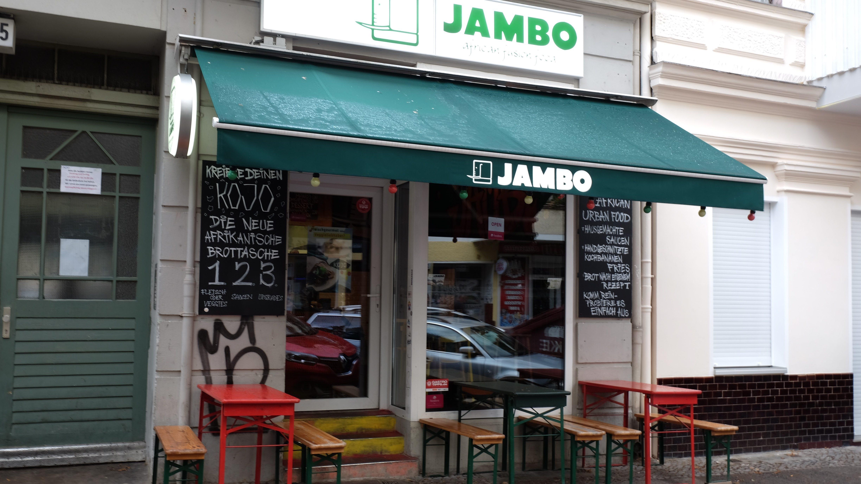 """Imbiss-Lokal von außem, mit weiß-grünem Schild """"Jambo"""" sowie Klapptischen und -bänken außen"""