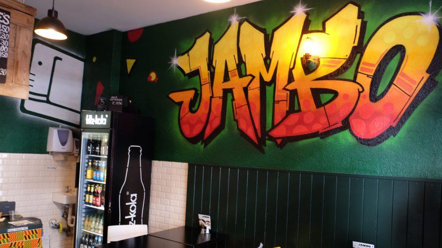 """Der Innenraum eines Imbiss-Restaurants, buntes """"Jambo""""-Graffiti auf grüner Wand"""