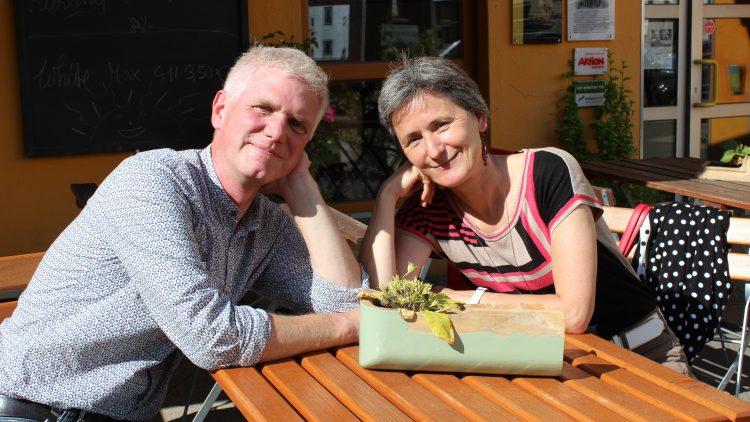 Jörg Fügmann und Iris Bauer von der Brotfabrik Weißensee sitzen an einem Tisch in der Sonne