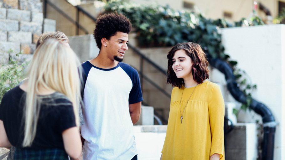Zwei weiße Mädchen und ein dunkelhäutiger Junge stehen redend auf der Straße.