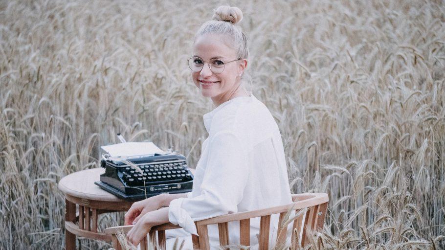 Autorin Julia Engelmann sitzt mit einer weißen Bluse, einer runden Brille mit Goldrahmen auf einem Holzstuhl vor einem Holztisch mit einer alten Schreibmaschine in einem Kornfeld. Die blonden Haare sind zum Dutt gebunden. Sie lächelt über die linke Schulter schauend in die Kamera.