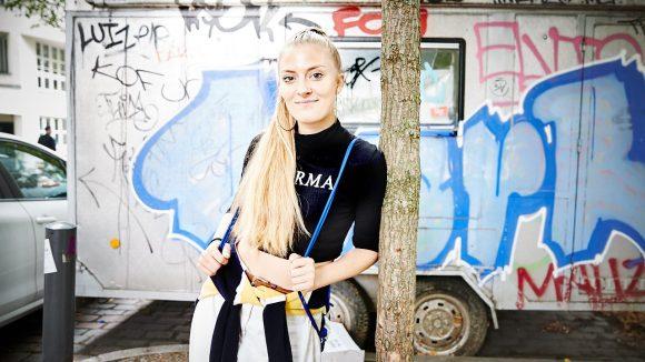 Kiddo Kat lehnt an einem Baum vor einem Container mit Graffiti.