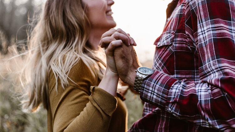 Junge Frau lacht jungen Mann an, halten Händchen