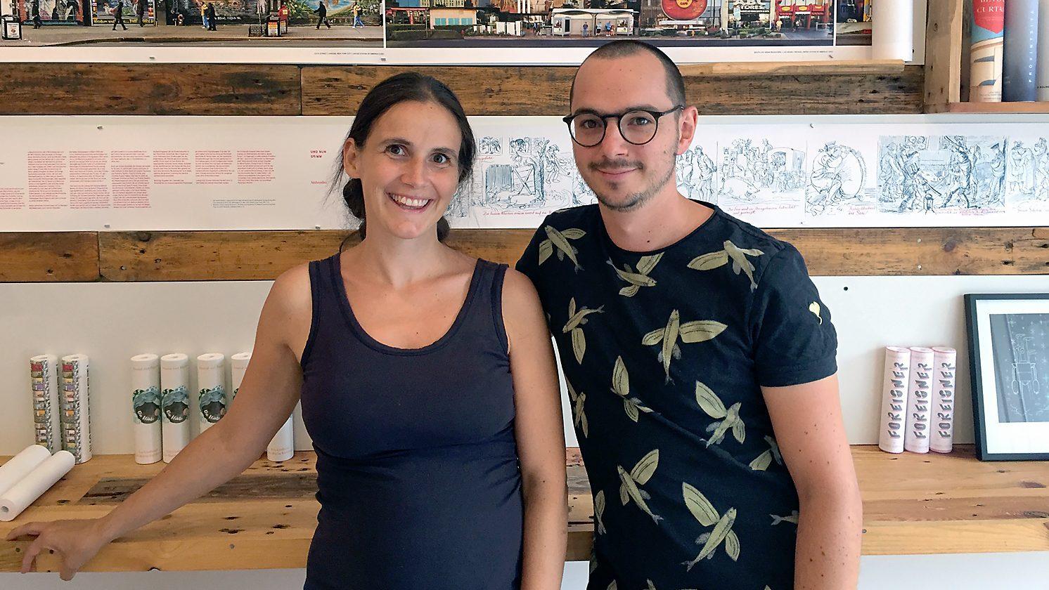 Eine schwangere, dunklehaarige Frau und ein junger Mann mit Brille stehen vor einer ausgeklappten Buchrolle.