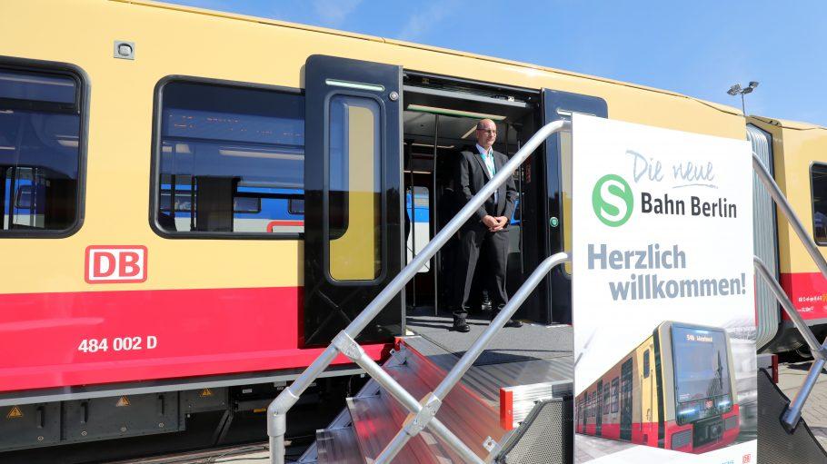 Ein neuer S-Bahn-Wagen der Berliner S-Bahn steht mit geöffneter Tür und einem Mann im Anzug davor bei der Messe Innotrans in Berlin.