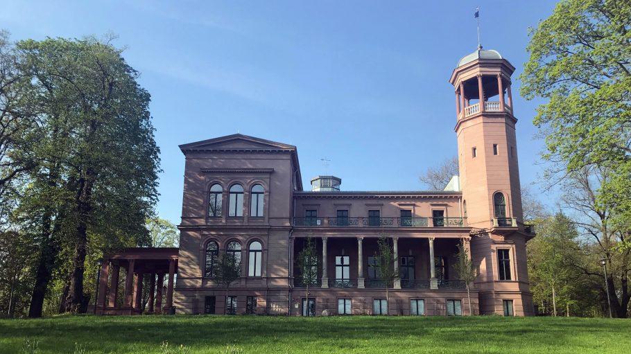 Schloss Biesdorf, eine spätklassizistische Villa mit Turm unter blauem Himmel, davor eine Wiese