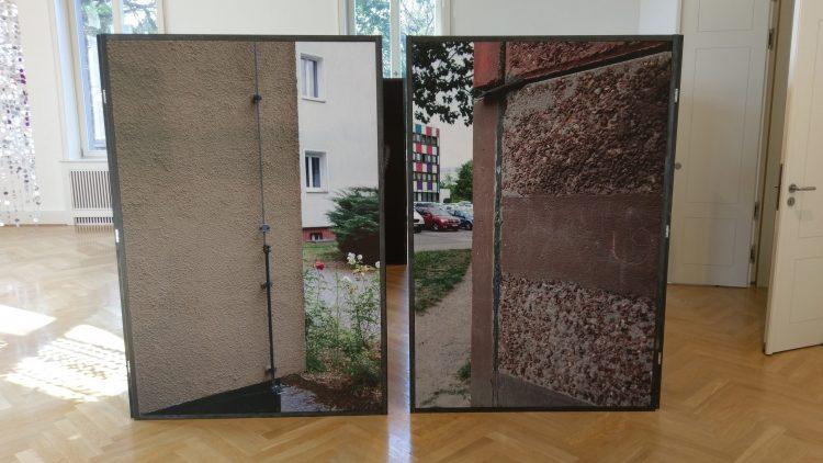 Zwei große Fotografien von Marzahn-Hellersdorfer Häuserecken stehen in einem Ausstellungsraum mit Parkett und weißen Wänden