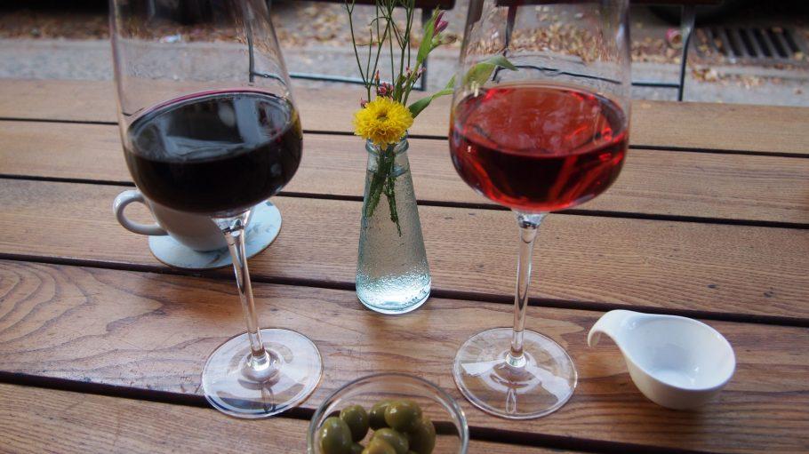 Ein Rosé Wein und ein Rotwein vor einer Blume stehen auf dem Holztisch, dvor steht eine Olivenschale.