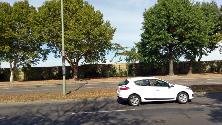 Sechsspurige Straße mit Mittelstreifen, dahinter Bäume, ein Zaun und ein landendes Flugzeug