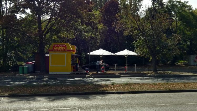 Gelb-rote Imbissbude mit weißen Sonnenschirmen und Tischen an einer großen Straße