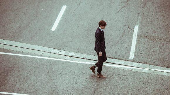 Ein junger Mann im Anzug überquert eine Straße