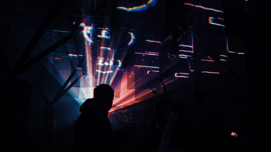 Ein Mann steht im dunklen Club mit Strahlern von hinten