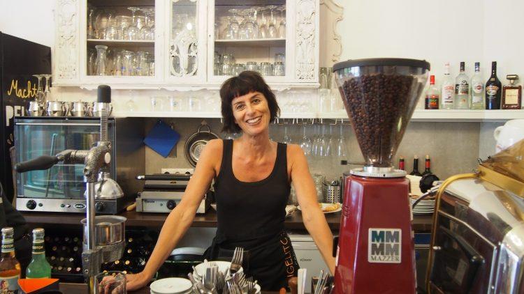 Die schwarzhaarige Besitzerin des Café Los Angelitos steht lächelnd hinter dem Tresen.