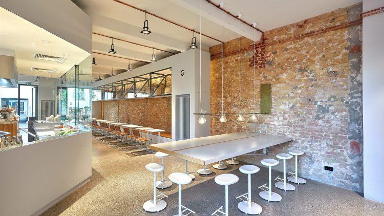 Leerer Innenraum des Arabica Cafés in Berlin, mit Ziegelsteinwand, weißen Tischen, Hockern und Lampen und einer verglasten Küche