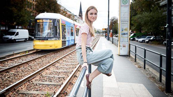 Die Schauspielerin sitzt auf der Stange neben den Tramgleisen, hinter ihr fährt eine Tram vorbei.