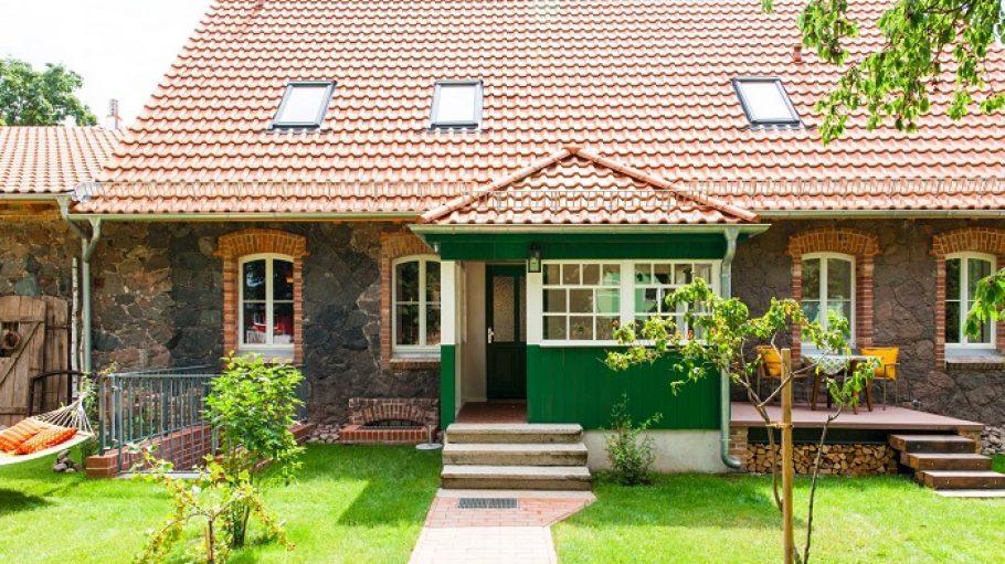 Das Haus von außen bei Sonnenschein und grünem Rasen.