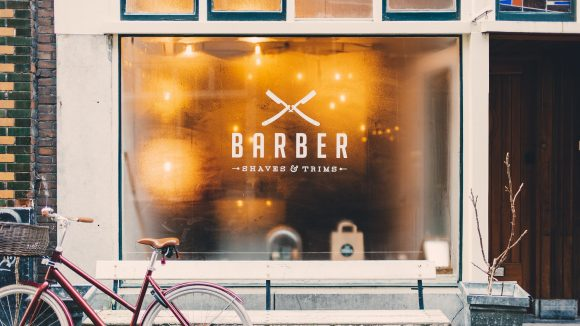 Rotes Fahrrad und Bank für einem Schaufenster mit Barber-Schriftzug