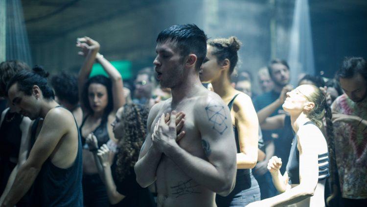 Mann mit nackten Oberkörper tanzt in der Menge.