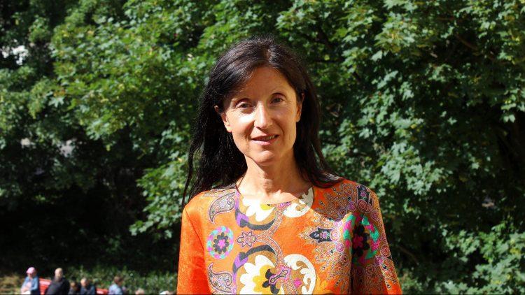 Brigitte Hausmann, Frau mit langen dunklen Haaren und orangem, floral gemustertem Oberteil, schaut in die Kamera, im Hintergrund Bäume