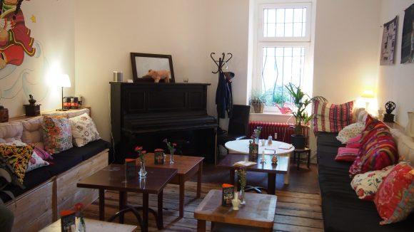 Das gemütliche Innere des Cafés mit Klavier, viel Holz und bunten Polstern.