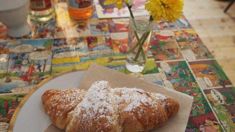 Ein Croissant mit weißem Puderzucker liegt auf einem Teller auf einem Tisch mit gelber Blume.