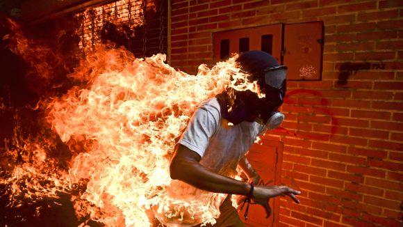 Ein brennender Mann rennt an einer Mauer entlang.