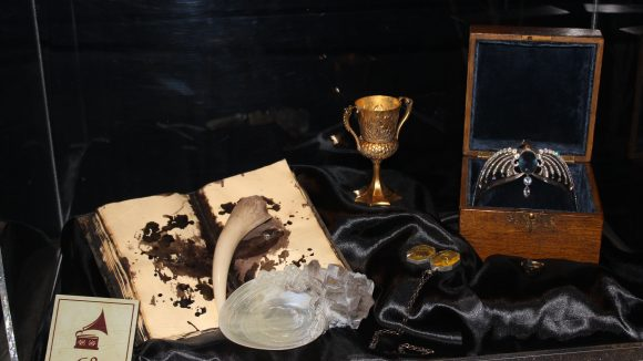 Die Originalrequisisten des zweiten Films Die Kammer des Schreckens: Rowena Ravenclaws Diadem und Salazar Slytherins Medaillon und Tom Riddles Tagebuch.