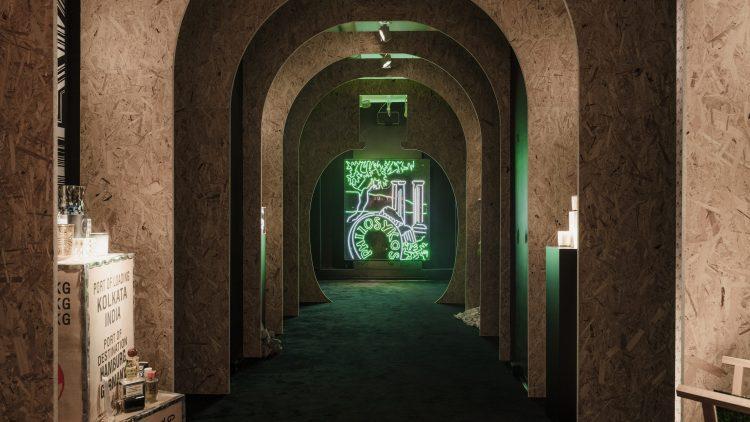 Gang aus Spanplatten, Parfumflaschen links und rechts, am Ende ein LED-Bild
