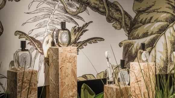 Vier Parfümflaschen stehen auf Säulen, im Hintergrund Wandbild von Dschungelbaum