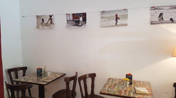 EIne Wand des Cafés mit Tischen an der Wand und Fotos an den Wänden.