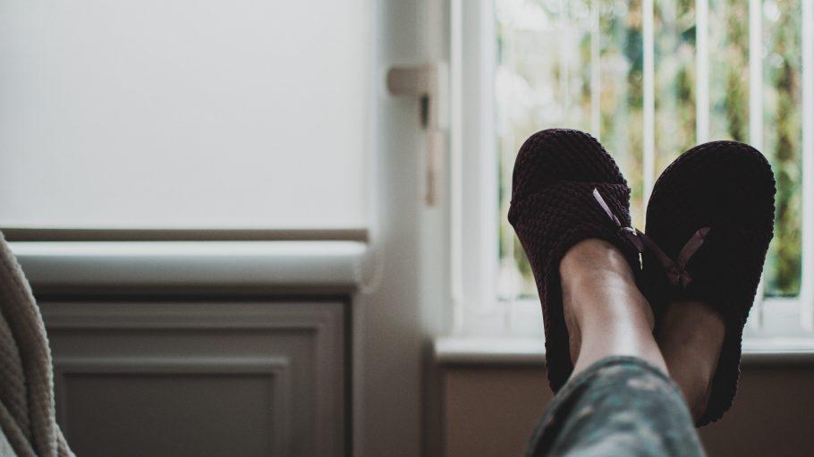 Frauenfüße mit dunkelroten Pantoffeln hochgelegt auf der Couch.