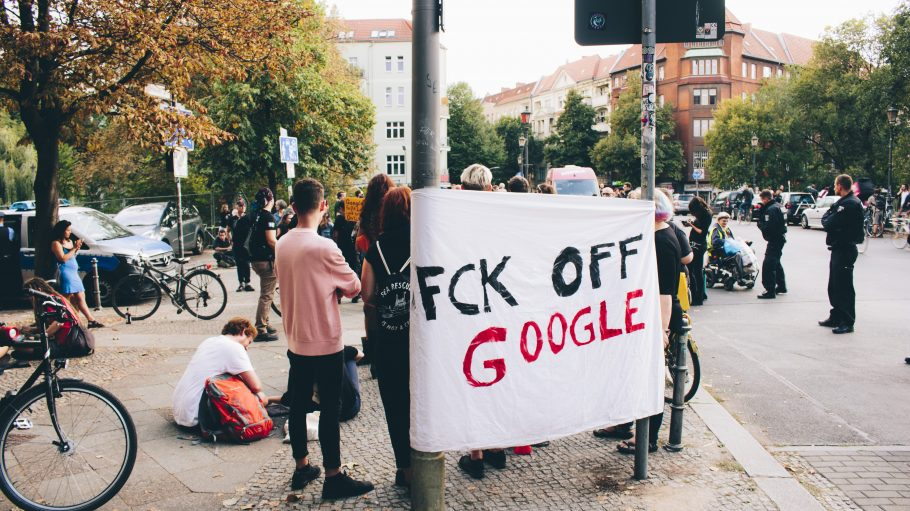 Demonstranten mit Fck off Google Plakat