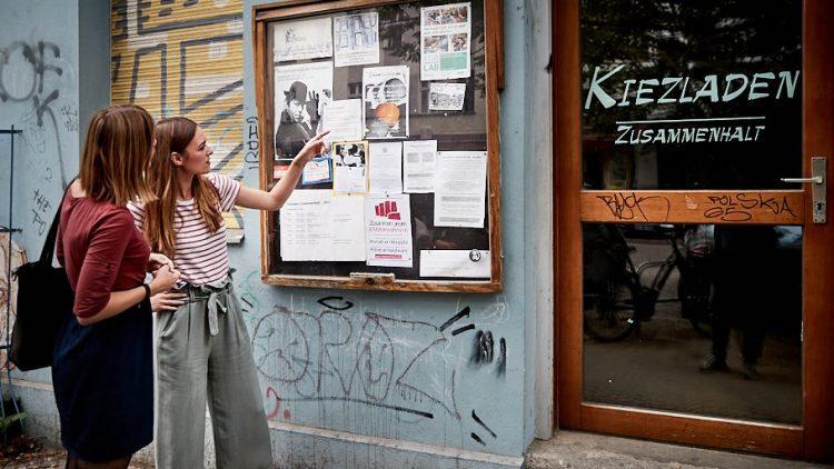 """Josephin zeigt auf ein Schild mit der Aufschrift """"Kiezladen"""""""