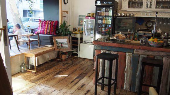 Der Eingang des Café Angelitos mit schöner Kuschelecke am Fenster, bunten Polstern und selbstgemachtem Tresen.