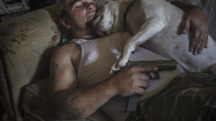 Ein schlafender Mann in Unterhemd, liegt mit Kanone und schlafenem Hund auf dem Bett.