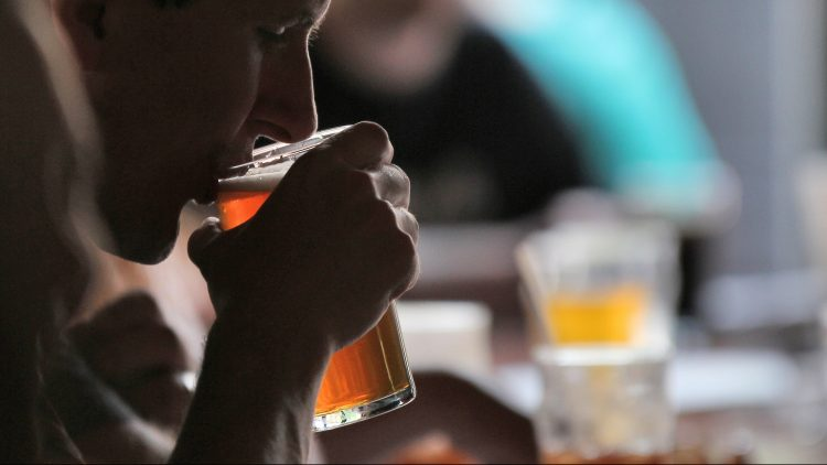 Nahaufnahme von Mann, der in Bar aus Bierglas trinkt