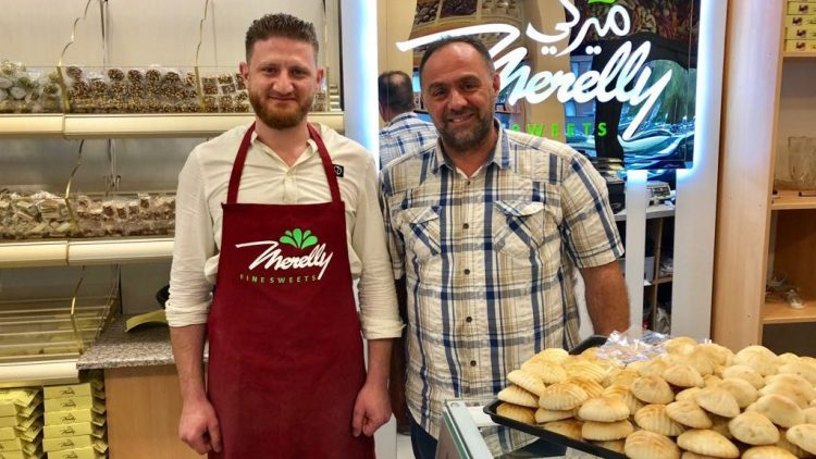 Ein junger Mann mit roter Schürze und sein Vater im karierten Hemd stehen nebeneinander in ihrer Bäckerei, im Hinter- und Vordergrund süße Backwaren
