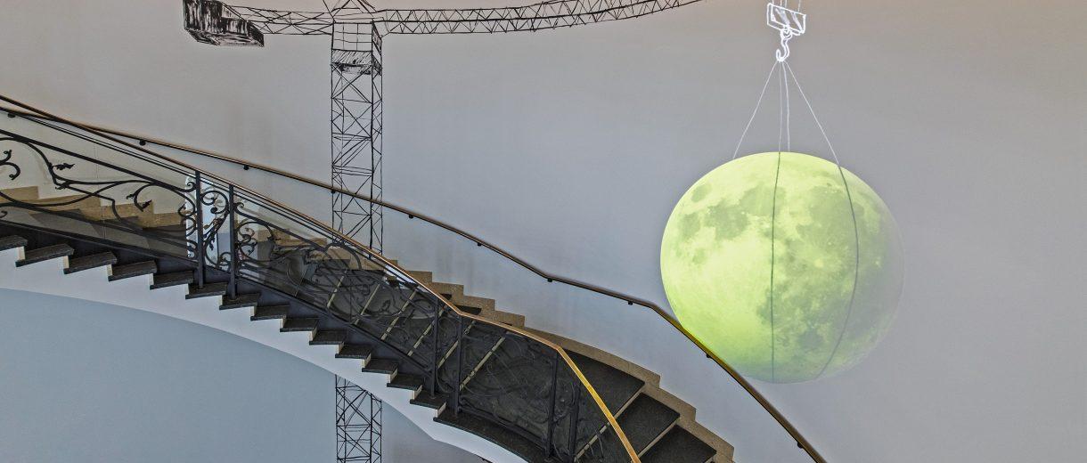 Ein an die Wand projezierter Mond im Treppenahus, der sich bewegt.