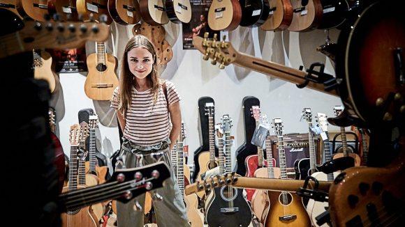 Josephin steht im Musikladen, umgeben von Gitarren.