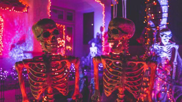 Zwei Skelette in Raum, der für Halloween geschmückt und schummrig rot beleuchtet ist.