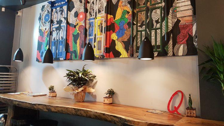 Ein buntes Wandbild über einem Holztresen.