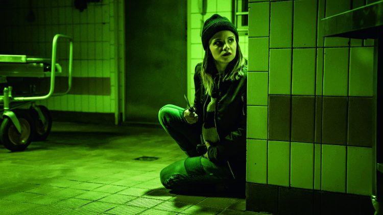 Frau sitzt auf dem Boden mit Messer in der Hand.